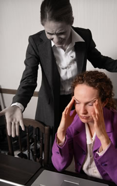 image of a visibly stressed female office worker sat at a desk while a female co-worker shouts at her.